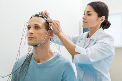 female doctor putting electrodes on patients head
